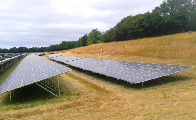Solar farm near Cambridge on a cloudy summer day working at full capacity