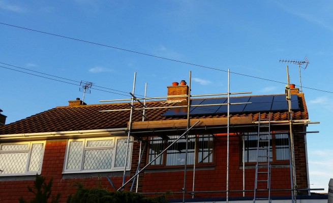 Three large and four small solar panels installed on a box gable type roof in Cambridge