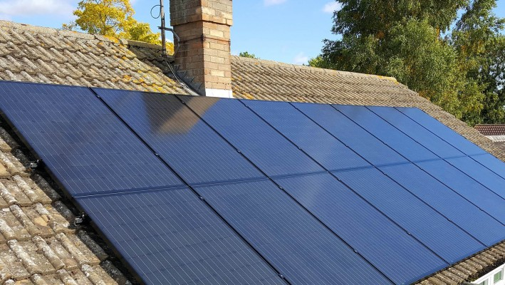 Sixteen solar panels on an open gable roof over a small bungalow in Cambridge