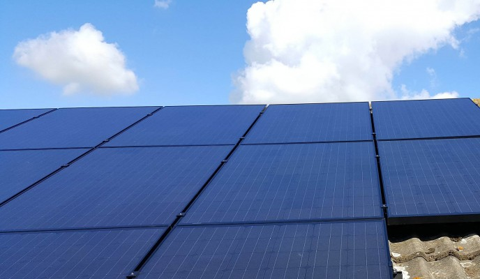 Multiple rows of solar panels installed on a roof in a house in Cambridge