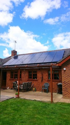 Medium bungalow house near Cambridge with two new rows of solar panels on a nice summer morning