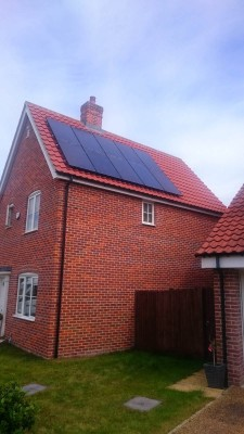 Large red brick semi-detached house with a set of ten solar panels near Cambridge