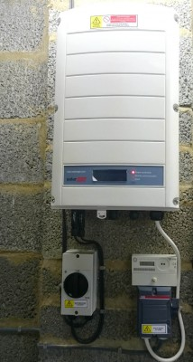 Solar panels inverter installed on a wall of a detached house in Cambridge